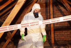 Asbestos Remediation - A specially trained worker wears protective clothing while clearing the asbestos.